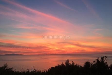 海越しの夕焼け空です。とてもいい天気の日だったので、空が真っ赤に染まっていて感動的な風景です。の写真素材 [FYI03160573]