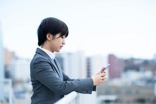 スマートフォンを操作するビジネスウーマンの写真素材 [FYI03161193]