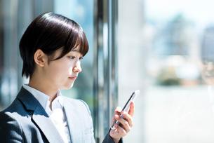 スマートフォンを操作するビジネスウーマンの写真素材 [FYI03161226]
