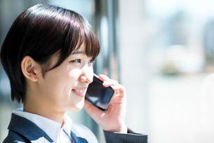 スマートフォンで電話をするビジネスウーマンの写真素材 [FYI03161227]