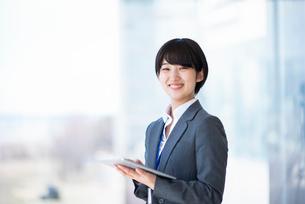 タブレットPCを持ち微笑むビジネスウーマンの写真素材 [FYI03161237]