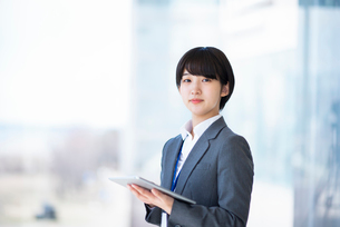 タブレットPCを持ち真剣な表情をするビジネスウーマンの写真素材 [FYI03161238]