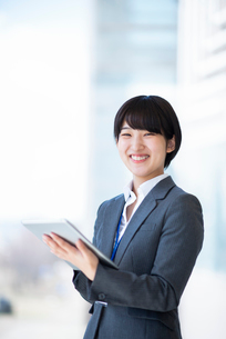 タブレットPCを持ち微笑むビジネスウーマンの写真素材 [FYI03161239]