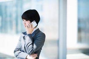 スマートフォンで電話をするビジネスウーマンの写真素材 [FYI03161257]