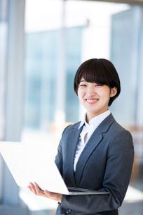 ノートパソコンを持ち微笑むビジネスウーマンの写真素材 [FYI03161263]