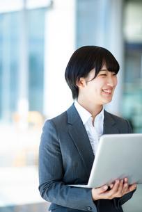 ノートパソコンを持ち微笑むビジネスウーマンの写真素材 [FYI03161264]