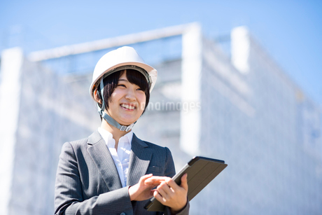 工事現場でタブレットPCを持ち微笑むビジネスウーマンの写真素材 [FYI03161288]