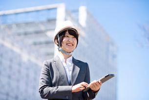 工事現場でタブレットPCを持ち微笑むビジネスウーマンの写真素材 [FYI03161289]