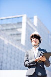 工事現場でタブレットPCを持ち微笑むビジネスウーマンの写真素材 [FYI03161290]