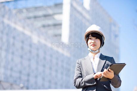工事現場でタブレットPCを持ち微笑むビジネスウーマンの写真素材 [FYI03161291]