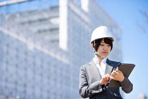 工事現場でタブレットPCを見るビジネスウーマンの写真素材 [FYI03161292]