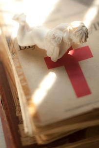 赤い十字の洋書の上の天使の写真素材 [FYI03162363]