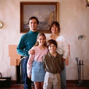 部屋でほほえむ両親と娘と息子の外国人4人家族の写真素材 [FYI03162368]