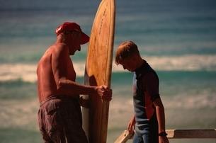 息子にサーフィンを教える父親 ケアンズ オーストラリアの写真素材 [FYI03162561]