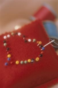 ハートに刺された針刺しのアップ(赤)の写真素材 [FYI03162737]