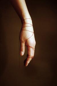 赤い糸を巻く手の写真素材 [FYI03162744]