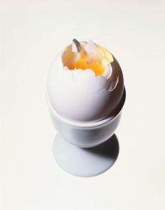 エッグスタンドに立った割れた半熟卵の写真素材 [FYI03162883]