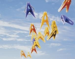青空に浮かぶ複数の洗濯バサミ(カラフル)の写真素材 [FYI03163076]