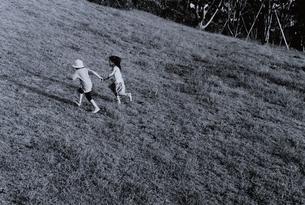 手を繋いで走る2人の日本人の子供 B/Wの写真素材 [FYI03163338]