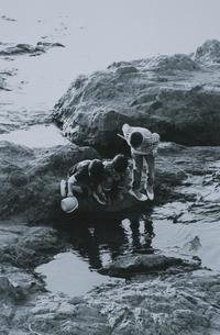 海岸の岩場で水中を見つめる3人の男の子 B&Wの写真素材 [FYI03163389]