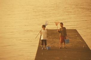 堤防で網とバケツを持つ2人の少年の写真素材 [FYI03163429]