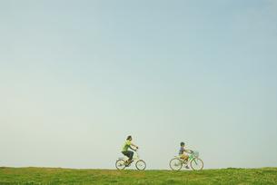 自転車で土手を走る少年と父親の写真素材 [FYI03163499]