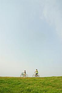 自転車で土手を走る少年と父親の写真素材 [FYI03163505]
