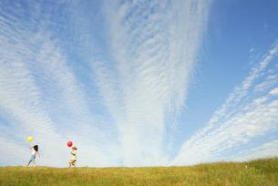 風船を持って歩く少年と少女の写真素材 [FYI03163508]