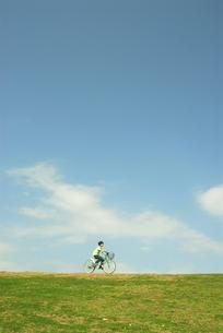 土手を自転車で走る男の子の写真素材 [FYI03163538]