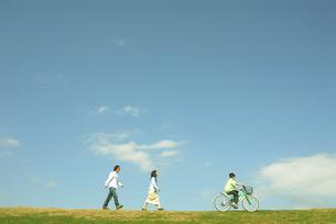 自転車に乗る男の子と後ろを歩く父と母の写真素材 [FYI03163544]