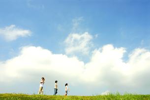 丘を歩く4人家族の写真素材 [FYI03163645]