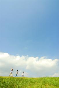 丘を歩く4人家族の写真素材 [FYI03163646]