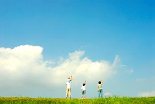 空に向かって手を振る4人家族の写真素材 [FYI03163648]