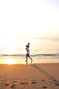 肩車をして夕景の海を歩く親子の写真素材 [FYI03163711]