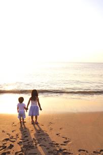 夕景の海を手をつないで見る姉妹の写真素材 [FYI03163715]