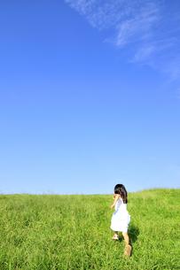 草原の丘を走る女の子の写真素材 [FYI03163716]