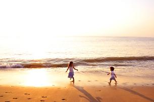 夕景の海岸を走る子供たちの写真素材 [FYI03163717]