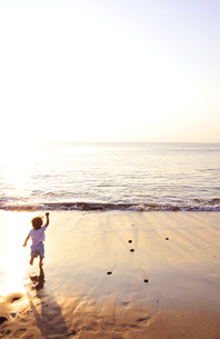 夕景の海岸を走る子供の写真素材 [FYI03163720]