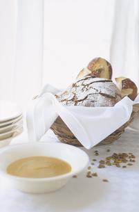 テーブルの上のカゴに入ったパンとスープの写真素材 [FYI03163834]