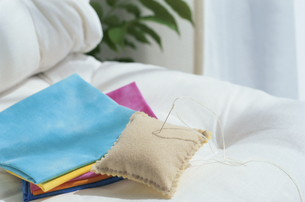 ソファの上に置かれた布と針山の写真素材 [FYI03163871]