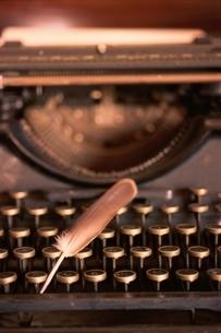 タイプライターの上の1枚の羽根の写真素材 [FYI03163975]