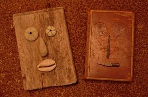 板と貝殻で作った顔イメージ(オレンジ色)の写真素材 [FYI03163977]