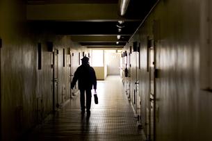 マンションの廊下を歩く男性のシルエットの写真素材 [FYI03164433]