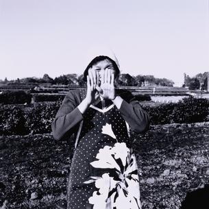 畑で顔を隠す日本人中高年農婦の写真素材 [FYI03164886]