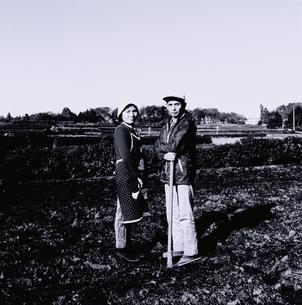 畑でくわを持つ中高年の農夫と農婦の写真素材 [FYI03164890]