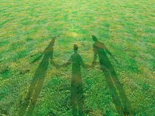 芝生に映る手を繋いだ親子三人の影のイラスト素材 [FYI03165774]