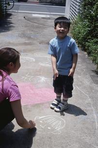 コンクリートにチョークで落書きをする男の子と女性の写真素材 [FYI03166309]