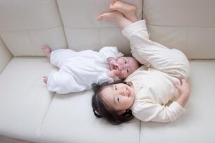 ソファの上で寝転ぶ赤ん坊と女の子の写真素材 [FYI03166390]