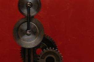 かみ合う鉄の歯車 赤バックの写真素材 [FYI03167106]