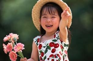 花を持つ麦わら帽子の日本人の女の子の写真素材 [FYI03167161]
